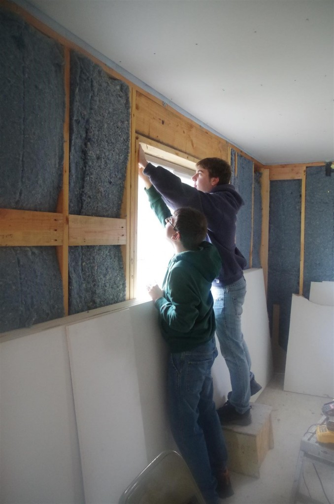 Volunteers install drywall.