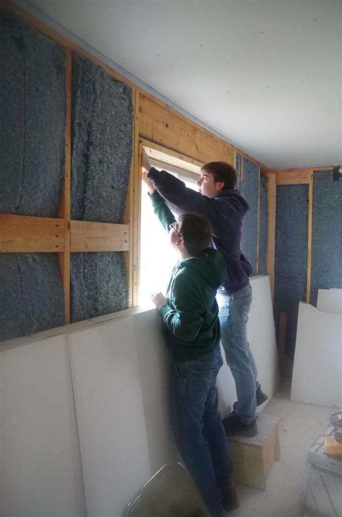 Volunteers install drywall.