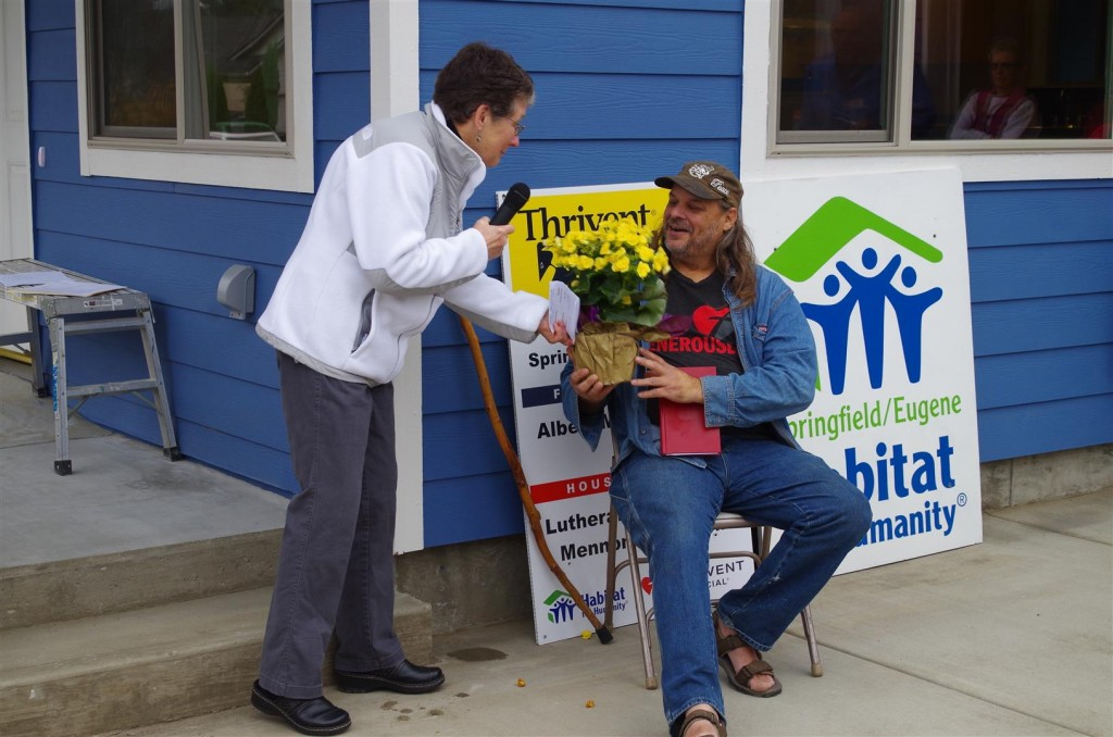 Shelley Turner, Habitat Board President, presents a gift to Albert on behalf of the Family Selection Committee.