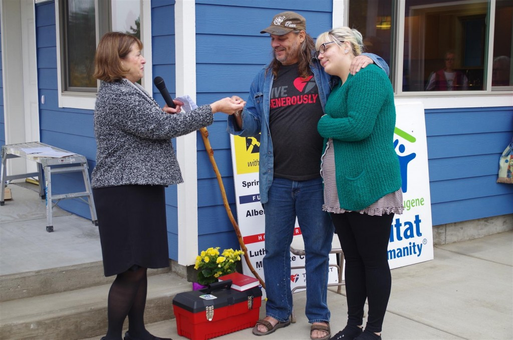 Albert and daughter, Angel, receive their house key from Lead Project Coordinator (and volunteer extraordinaire), Cathy Olson.